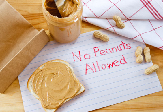 Peanut butter and peanuts on a table with a crayon drawn sign reading 'No Peanuts Allowed'