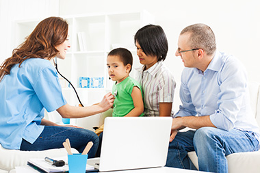 Female doctor listening to child's heart, with mom and dad providing support.